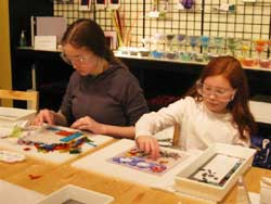 Two girls making glass